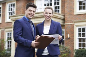 Male And Female Realtor Standing Outside Residential Property in Worcester County MA